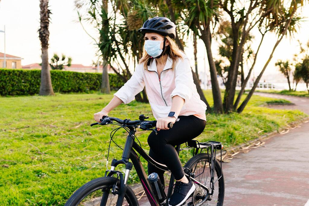 mujer pedaleando con mascarilla covid 19