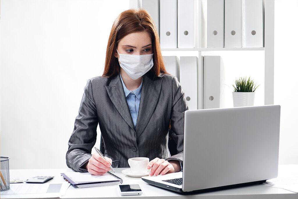 Empleada trabaja con mascarilla en la oficina lista para la nueva normalidad